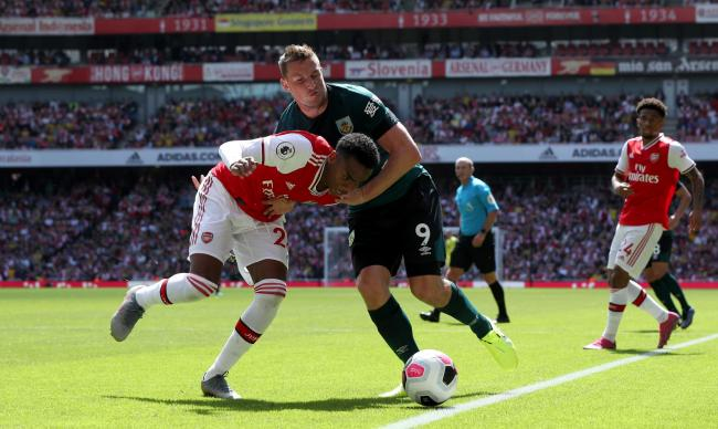 Arsenal's Joe Willock (left) and Burnley's Chris Wood battle for the ball during the Premier League match at The Emirates Stadium, London.