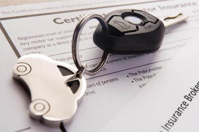 A generic photo of car keys on insurance documents