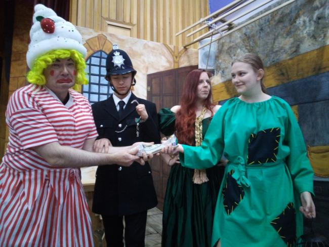Pictured in rehearsal is one of the Ugly Sisters, Molly Brolly (played by Father Nicholas Davis) being arrested as she tries to take charge of the glass slipper held by Cinderella (Tabitha Mossley) watched by Baroness Latrina (Adelle Walmsley) and Constab