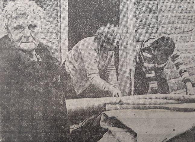Edna Smith watches as her relatives sort out the flood damage