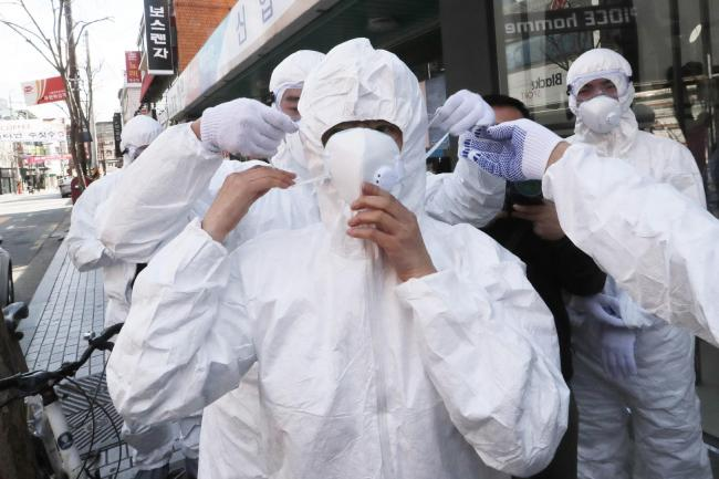 A worker wears a face mask to spray disinfectant as a precaution against the coronavirus at a shopping street in Seoul, South Korea, Thursday, Feb. 27, 2020. South Korea and China each reported hundreds more virus cases Thursday as the new illness persist