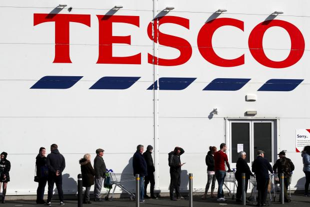 Lancashire Telegraph: People queue outside a Tesco Extra store in Madeley, Shropshire