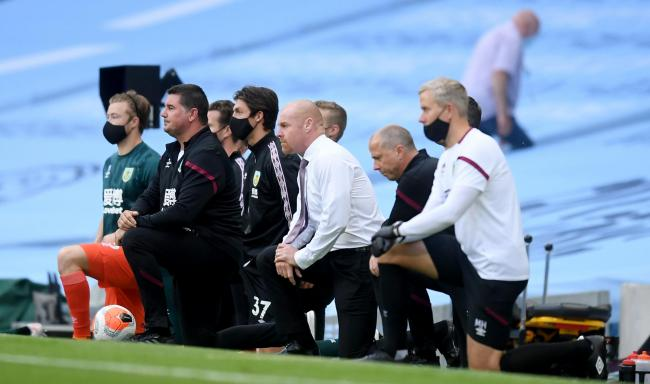 Burnley boss Sean Dyche and his staff take a knee in support of Black Lives Matter