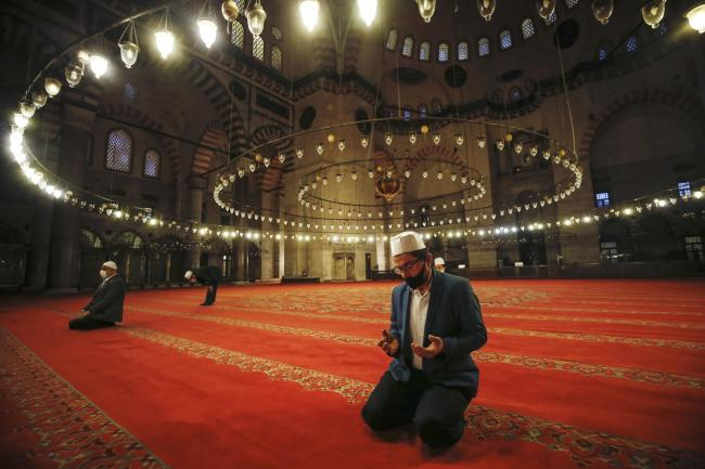 Staggered people offer the Eid al-Fitr prayer amid concerns of the coronavirus outbreak at the historical Suleymaniye Mosque in Istanbul, early Sunday, May 24, 2020. Muslims in the world are marking a muted and gloomy religious festival of Eid al-Fitr, th
