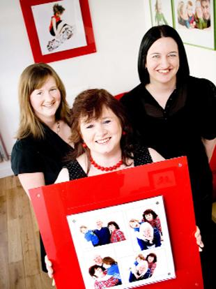 ONE OF A KIND: Heather Murphy (centre) is presented with a framed family portrait by Maria Broadhurst (right) from Autograph Portraits, watched by Joanne Clark from Global who ran the competition