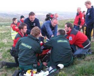 TREATMENT: Paramedics and Bolton Mountain rescuers attend to the injured cyclist