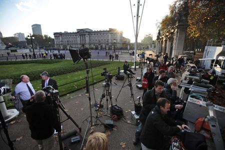 Members of the media work on the story of Britain's Prince William engagement, across the street from Buckingham Palace, background, in central London.
