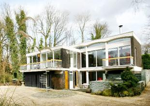 FOR SALE: Domus comes with gardens, a double garage and 5.7 acres of land. Inside it has wood-panelled walls, built-in oak furniture, acoustic lined ceiling and original bar with rosewood drinks shelving