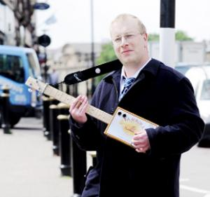 RECYCLING Andrew Deighton strums a guitar made out of a cigar box,