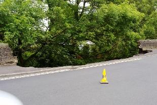 DANGER The section of road with has collapsed into the brook