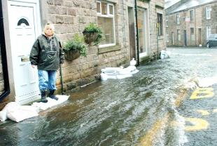 SANDBAGS Christine Sutehalls on her doorstep in Whalley Road, Sabden, when it flooded in 2008