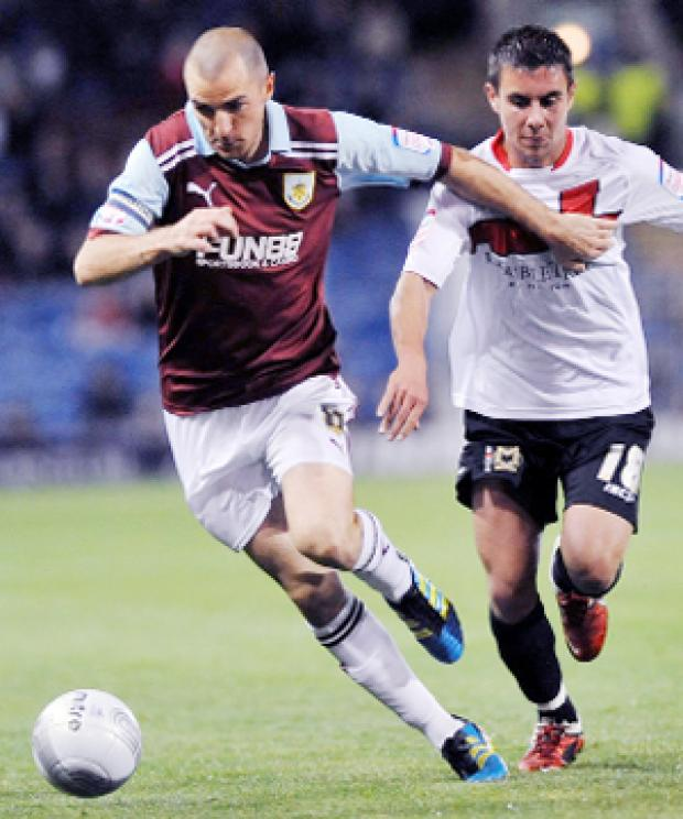 BATTLE Dean Marney runs away from MK Dons' George Baldock