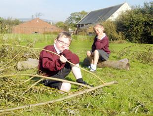 UPSET Mason Eardley and Annie Randall, both six, look at what's left of three trashed willow shelters at the school