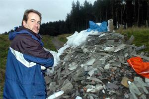 DUMPED Environmental crime officer Richard Waters examines building waste left on land near Delph Reservoir, Belmont