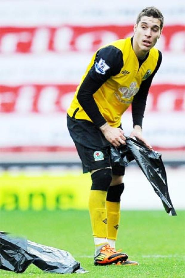 CLEAR UP Rovers scorer Ruben Rochina picks up the bin liners which floated across the Britannia Stadium pitch