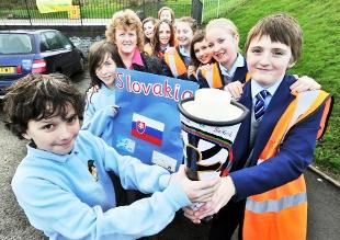 HANDOVER Brownedge St Mary's pupil Michael Duerden (right) hands over the Prayer Torch to St Joseph's RC Primary School head boy prefect Pablo, watched by head girl prefect Caitlin, head teacher Anne O'Brien and fellow pupils from the Bamber Bridge