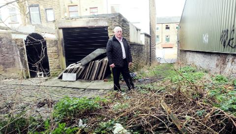 Coun Neil Butterworth in the alleyway that is causing concern