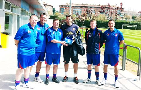 Nigel Dixon hands over a friendship plaque to a Barcelona junior coach