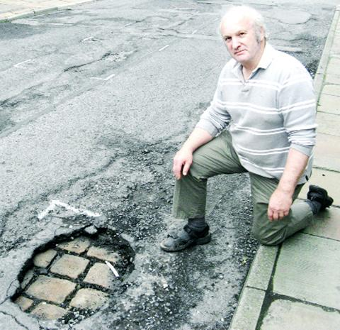 Coun Simon Hugill shows cobbles exposed by deteriorating tarmac