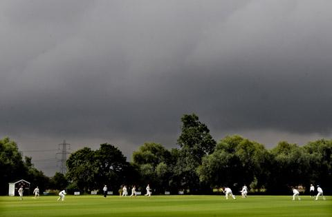 Lancashire Telegraph: A shaft of sunlight illuminates play between Sheriff Hutton Bridge and Dunnington as rain clouds gather above on another weather-hit day