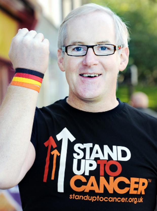 John Ellison is promoting the Stand up to Cancer wristband campaign