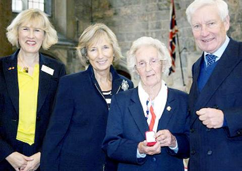 Kay Pinfold receives her award from Lord Crathorne, Lord Lieutenant of North Yorkshire, watched by Christine Harris, Deputy Lord Lieutenant of West Yorkshire, and Sue Collins, head of WRVS for the North West, Yorkshire and Humber