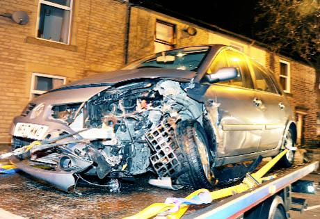 DAMAGE The Renault Scenic is reovered from the scene of the collision and, right, the demolished wall