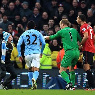Rio Ferdinand, right, was hit by a coin during the Manchester derby