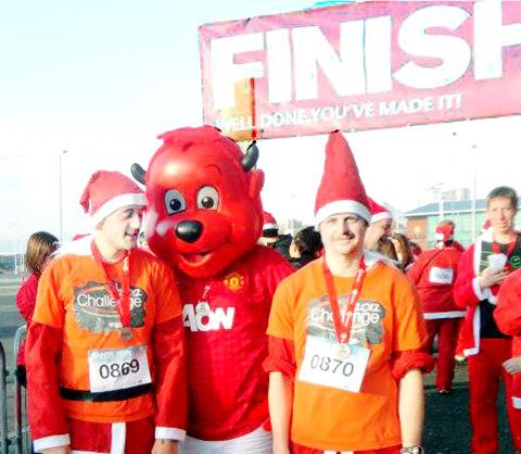 RED LETTER DAY Ben Zebrowski and Matthew Clawson with mascot Fred the Red at the Manchester United Santa Dash