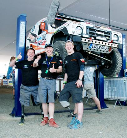 Corporal Tom Neathway, Justin Birchall and Corporal Phillip Gillespie in the bivouac garage preparing one of the team's Wildcat race vehicles, in Lima, Peru, before the Dakar Rally
