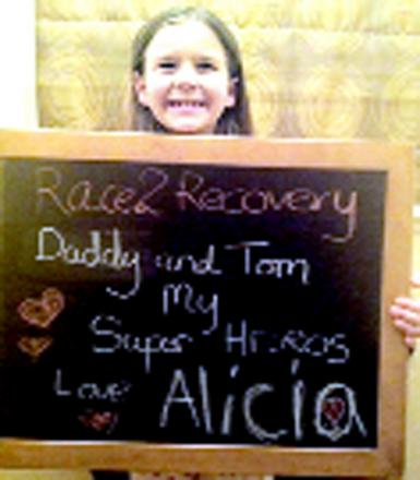 Alicia with her message to her dad