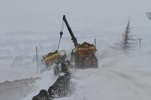 Lancashire County Council gritter being pulled out of snow drift in Blacko
