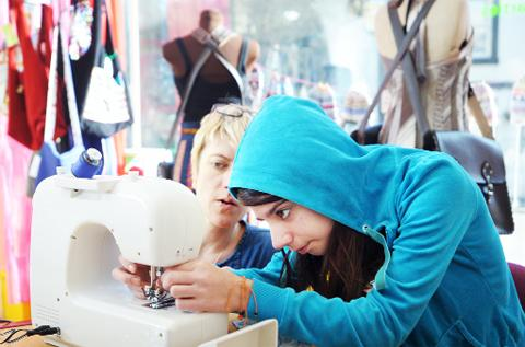 Tansy Dyer gives India Maccabe a sewing lesson