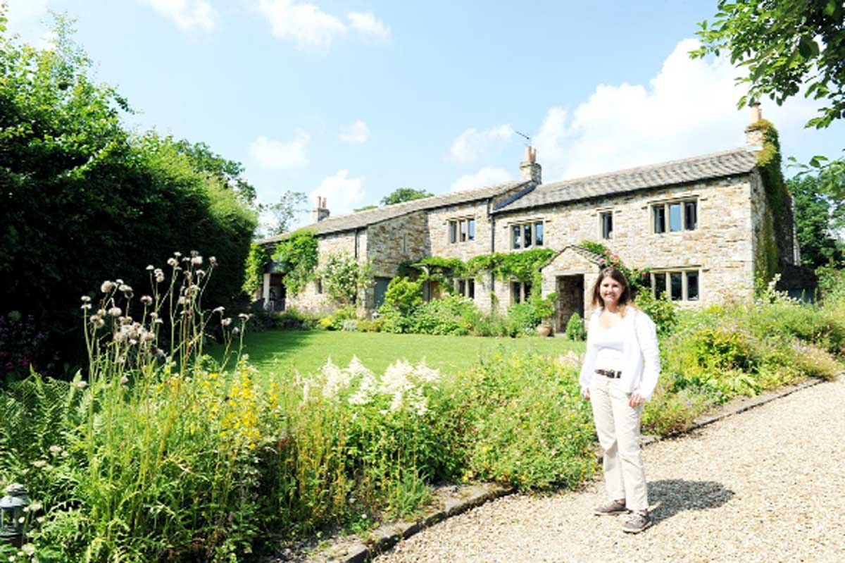 Sue Farmer by her front lawn, and, below, working in one of her gardens at Varley Farm