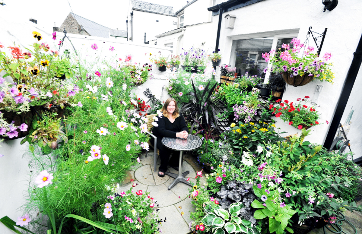 Vicky Cronshaw  in the garden in the back yard of her terraced home