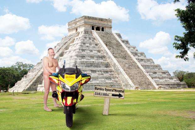 A biker poses in front of an Aztec pyramid