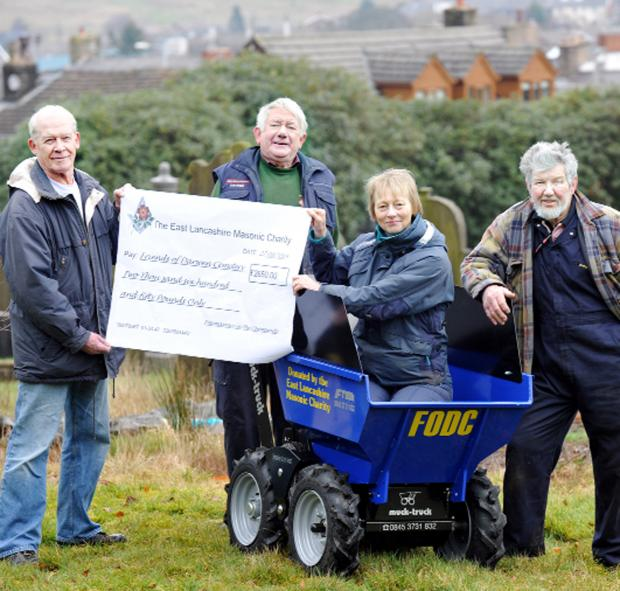 Lancashire Telegraph: Terry Woods, of East Ribble District Freemasons, presents the funds to cemetery friends group members Colin Briggs, Jill Marr in the 'muck truck' and Mick Walsh