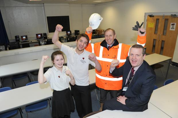 Head Girl Emily Cox, 15, joins Head Boy James Goodall, 15, along with Mike Burridge, Keepmoat Project Manager, and Craig Baker, Headteacher, as they celebrate the news that this maths room will be turned into a new common room.