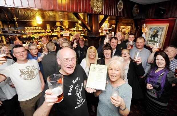 E Lancs Camra chair John Webster presents Kathryn Ratcliffe with the award watched by regulars at the Rifle Volunteer