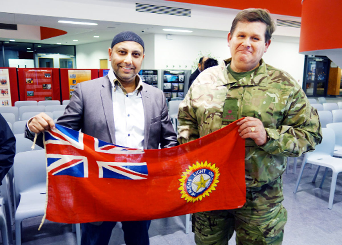 "Faz Patel and Major Bob Smethers holding the Flag of British India ""Star of India"" Red Ensign version from WW2."