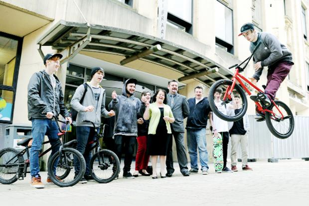 Mike Curley shows off his bike tricks watched by Coun Kate Hollern, Coun Trevor Maxfield, skaters and bikers