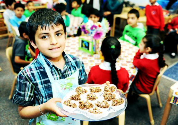 Daud Ali, 6, serves chocolate crispy cakes at Whitefield Infant School, Nelson, at a recent Fairtrade cafe