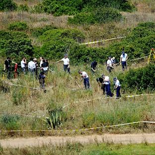 British police and their Portuguese counterparts search a patch of scrubland on the Algarve