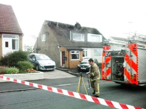 A firefighter at the home in Dunster Avenue, Oswaldtwistle