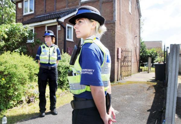 Police support officers stand guard outside the scene in Borrowdale Avenue, Blackburn