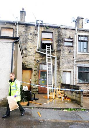 Police at the scene of the fire in a flat above a tattoo shop on Accrington Road, Burnley