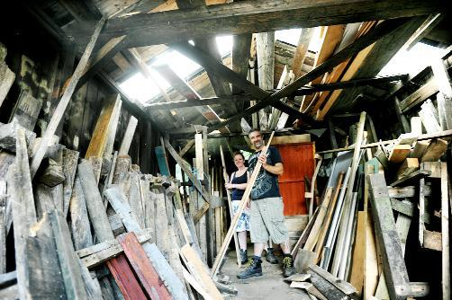 Volunteer supervisor Sam Harrison-Millward and volunteer Sharon Macdonald in the woodshed where they have been having to break donated wood into pieces by hand