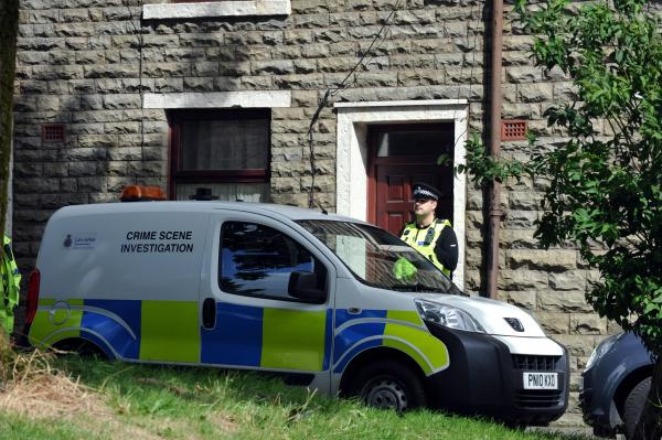 Police guard the house on Deardengate Croft, Haslingden, after the  early  morning attack