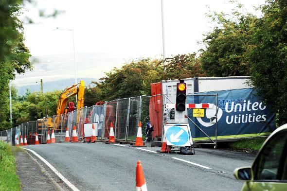 The temporary traffic lights are to remain on Grane Road which has one lane closed to enable United Utilities engineers to repair the collapsed sewer