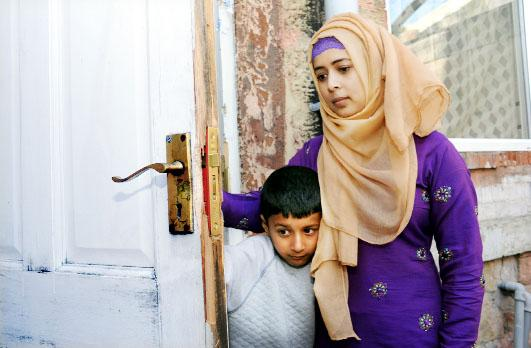 Rujina Begum and son Ridwan with the damaged door of her house in Clegg Street East